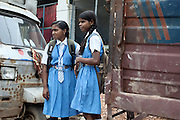 Schoolgirls in uniform are waiting for a rickshaw on the streets of Varanasi, Uttar Pradesh, India.
