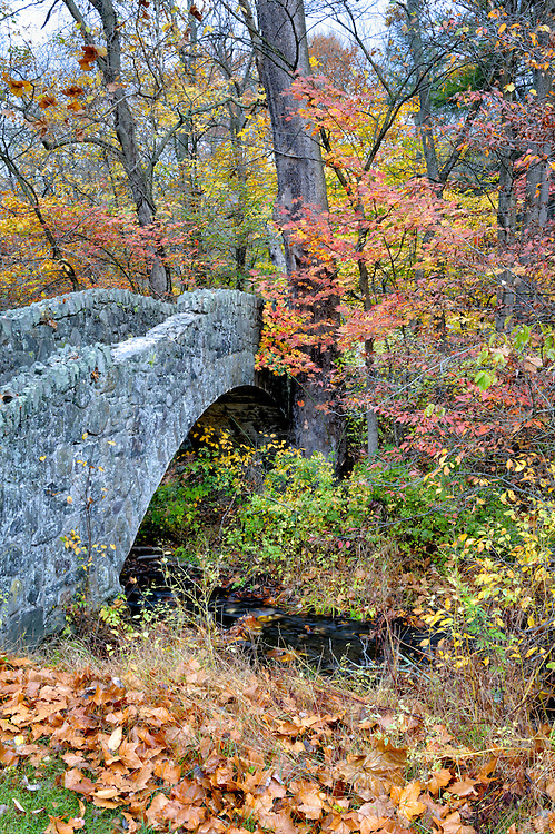 Stone arch bridge over small stream in the late fall woods near Buttermilk Falls at East Stroudsburg, PA.