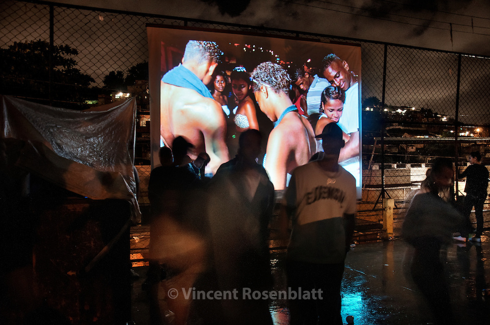 Baile Funk in the favela Arvore Seca, in the district of Lins, Rio de Janeiro. On the screen, a slideshow of Vincent Rosenblatt's photos. After years documenting Baile Funk in the whole city - he started to show it back in the place where the work was done.