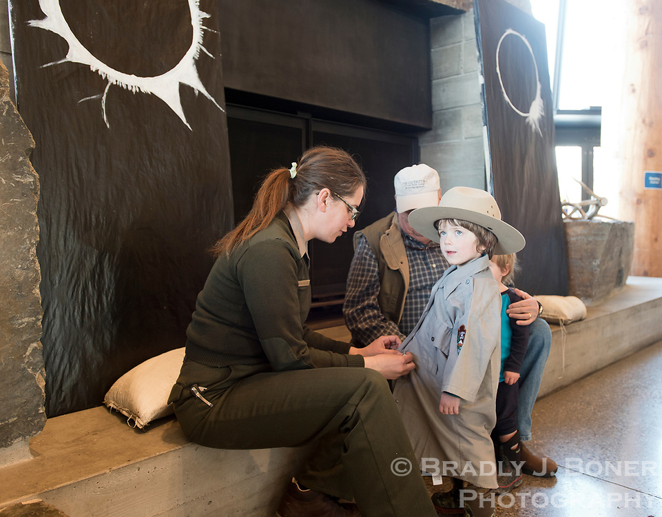 Graham Whitaker, 4, of Jackson, gets outfitted in a National Park Service ranger outfit by interpretative ranger  Sabrina Pitcher during Junior Ranger Day at the Craig Thomas Discovery and Visitor Center on Saturday in Grand Teton National Park.