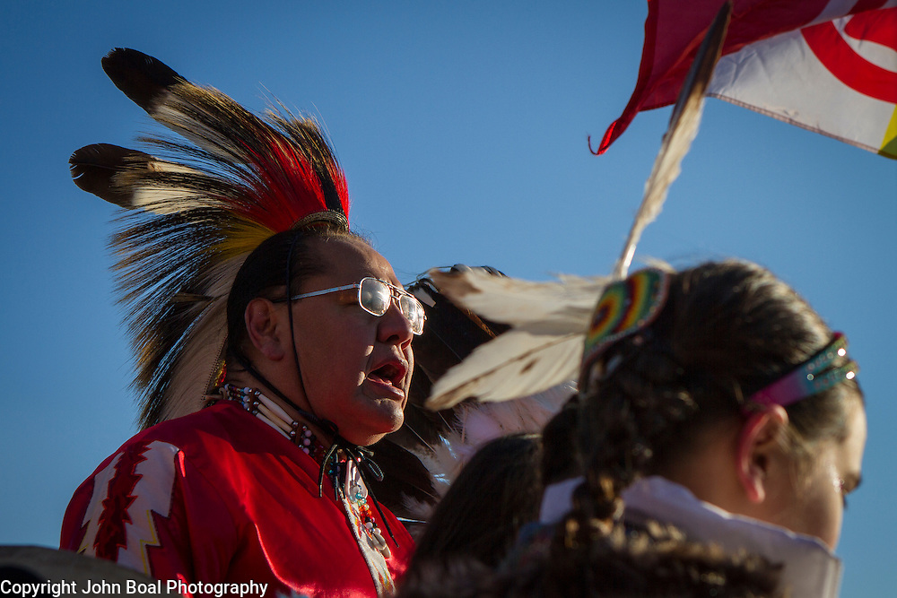 Beneath the American Indian Movement flag, Dennis Zotigh, Kiowa, left, sings and drums with family members during a protest and march from in front of the U.S. Capitol to the EPA, about the North Dakota Access Pipeline, as well as the effort to free Leonard Peltier.  Saturday, December 10, 2016. John Boal Photography