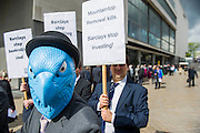 Protestors complaining about the use of tax havens, banks support for coal mining (pictured) and the lack of a robin hood tax on financial transactions gather outside the Festival Hall as Barclays plc shareholders queue for the bank's AGM. Southbank, London, UK 24 April 2014.