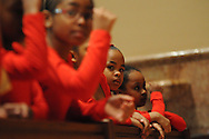 "From the front pew of Holy Name Cathedral, Christen Jones, 7 (in focus), listens to a homily with other Chicago Catholic School liturgical dancers during the 33rd Annual African American Heritage Month Eucharistic Celebration at Holy Name Cathedral. This year's mass celebrates the the Nguzo Saba principle of Kuumba, or ""creativity"" at Holy Name Cathedral."