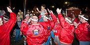 610 Stompers, while  marching in the Muses parade, spontaneously raise up a happy little boy