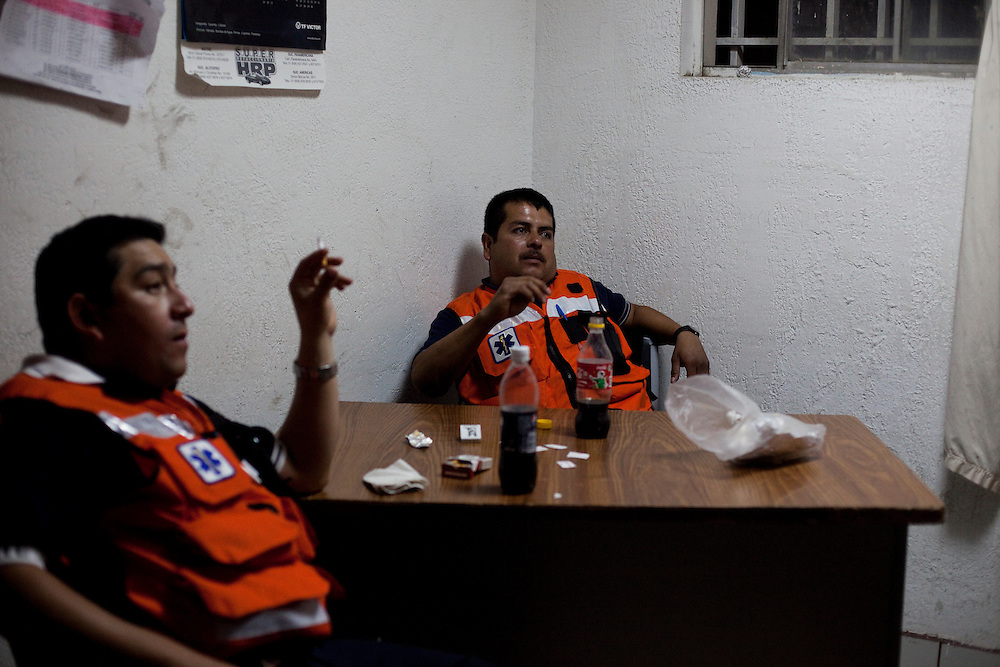 Rescue workers smoke while waiting for something to happen in Ciudad Juarez, Chihuahua Mexico on May 4, 2010. ..