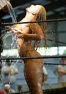 """Alexis"" showers off between rounds while wrestling with another woman in chocolate sauce at a Harley-Davidson anniversary party in Milwaukee August 29, 2003. The legendary American motorcycle company is celebrating its 100th anniversary and is expected to draw 200,000 to 300,000 people to the companies home base over four days.    REUTERS/Rick Wilking"