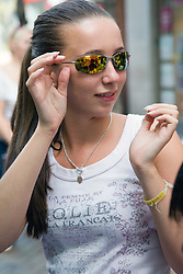 Teenager girl trying on sunglasses,