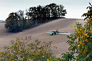 tractor with crop sprayer spraying herbicide or insecticide on a pre emergent farm field France