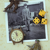 Vintage black and white photo of 1960s boy in school uniform and cap in garden lying with old watch three dice and two lead model soldiers