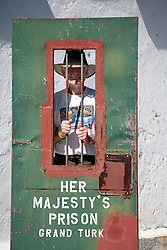 Grand Turk Island: Tourist poses behind bars at the old island prison in Cockburn Town.