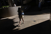 Woman walks through area of City of London sunlight.