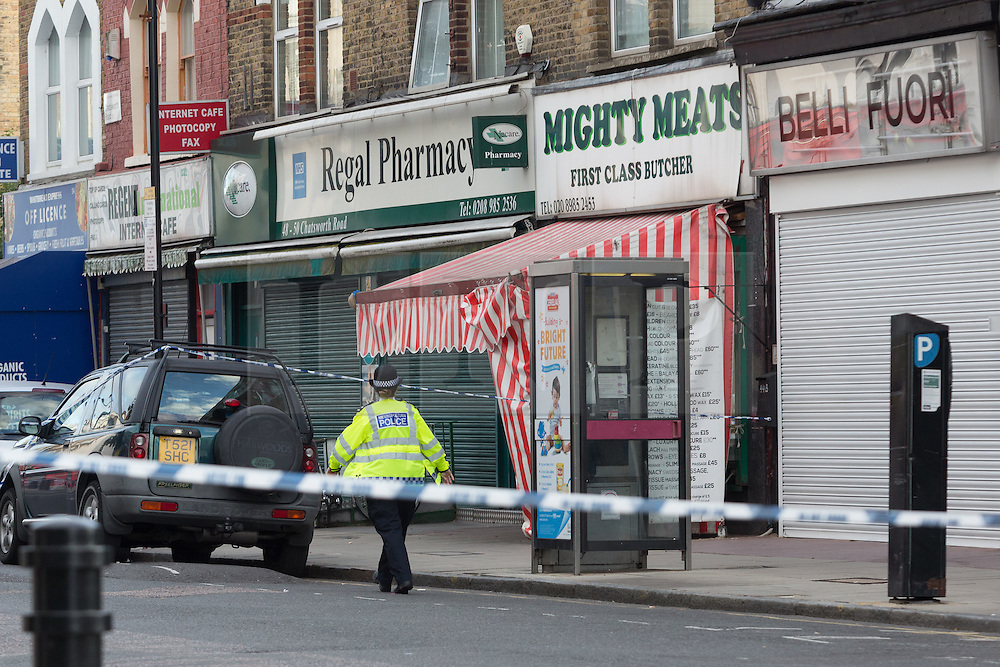 © Licensed to London News Pictures. 27/09/2015. London, UK. A police officer walks past Regal Pharmacy inside the police cordon on Chatsworth Road. Police have launched a murder investigation after a man was shot dead in the street outside Regal Pharmacy next to Mighty Meats butcher shop in Chatsworth Road, Hackney, east London yesterday. Photo credit : Vickie Flores/LNP