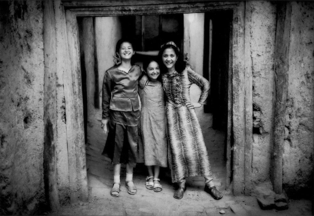 Uighur girls in the doorway of their mudbrick home in the old city of Kashgar, a city perfectly suited to the extremes of hot and cold of Chinese Turkestan.