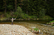 Young woman fishing the Bull River where the East Fork Bull River comes in at the Bull River Guard Station, one of the original ranger stations on the Kootenai National Forest now used as a cabin rental. Bull River Valley, northwest Montana.