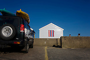 Expensive real estate beach hut at 4x4 car at the Suffolk seaside town of Southwold, Suffolk.