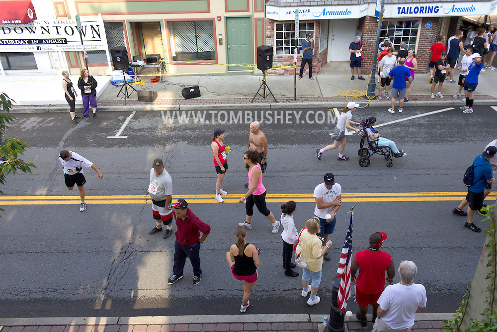 Middletown, New York - People warm up and walk along North Street before the 2012 Run 4 Downtown road race on Saturday, Aug. 18, 2012.