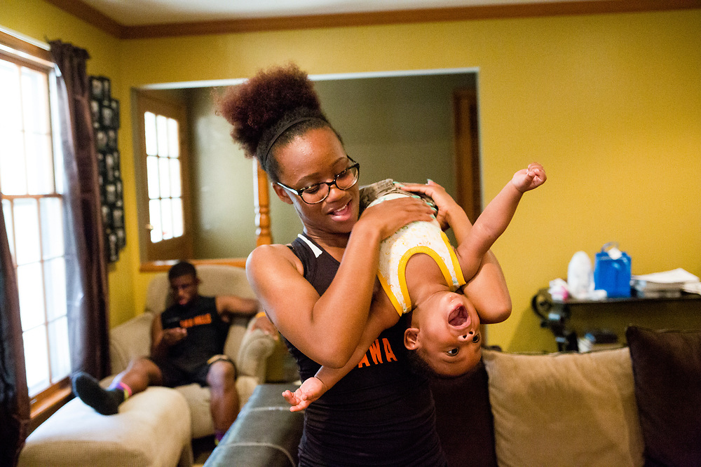 "Alexis Lowe, 18, plays with her 10-month-old son Zayden Lowe in the living room of her south-side Grand Rapids home after running in a track meet Tuesday, May 24, 2016. Alexis gave birth to Zayden about a month before she started her senior year at City High School. ""I've never felt so important in my life,"" she said. ""I just gave life to somebody else and I just put another person on the earth. I feel like that was such an accomplishment. That was the most important thing I ever did in my life."""