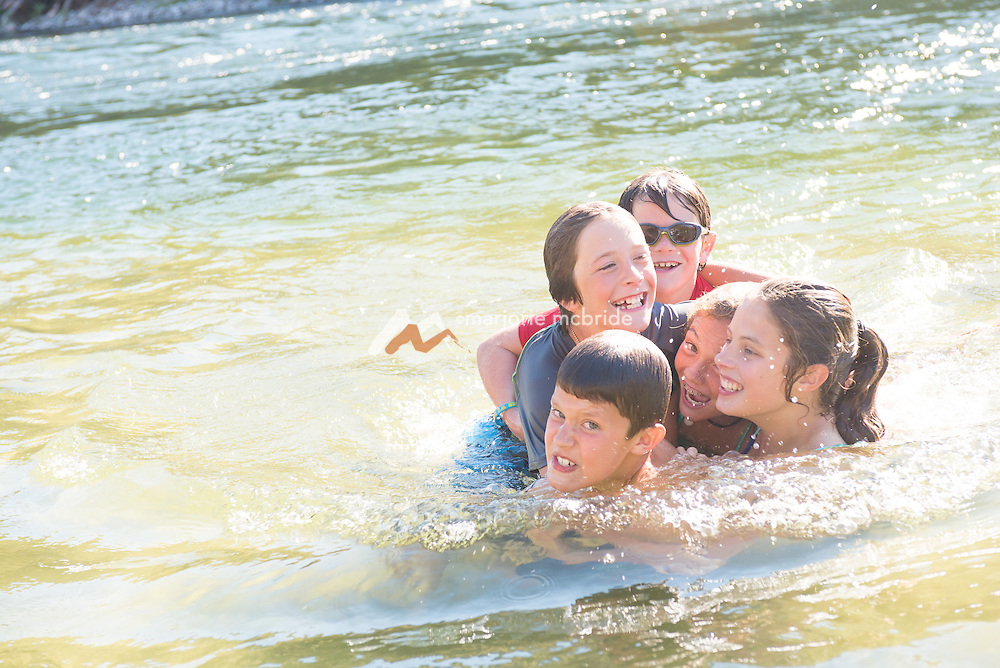 A pile of kids wrestling and laughing in the water on the river during a rafting trip on the Main Lower Salmon River, Hammer Creek to Hellar Bar, Idaho.