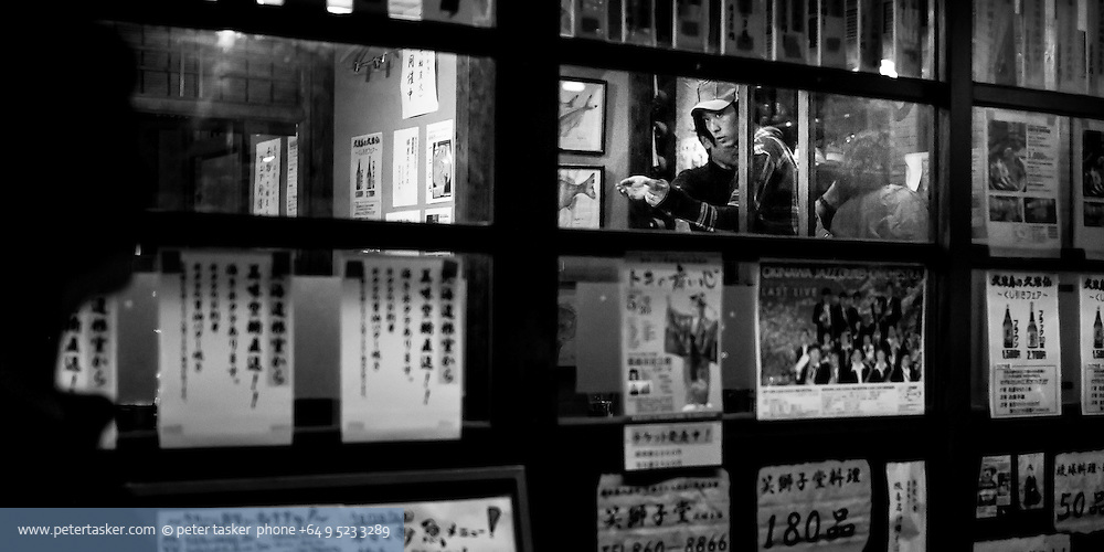 Naha, Okinawa, Japan.  Man entering restaurant at night.  Photographed while walking by.