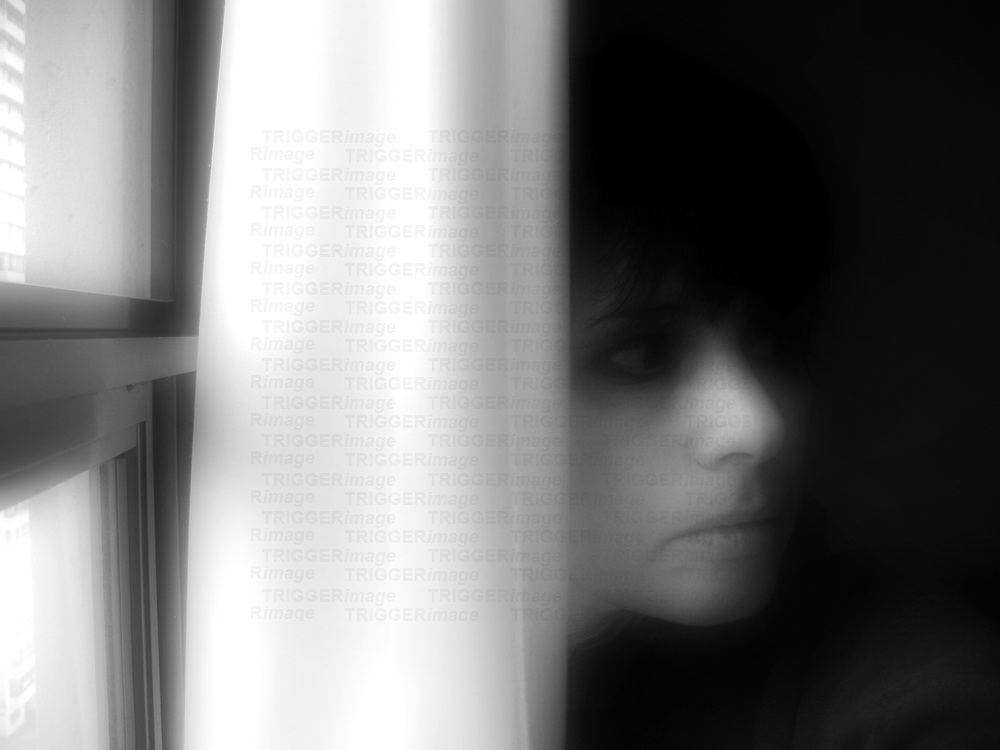 The face of a young woman beside a curtain