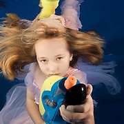 underwater portrait of little girl (8 years old) holding watergun in swimming pool