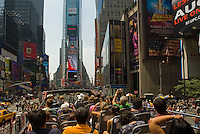 Tourists on a double-decker tour bus drive towards Times Square in New York City, NY, USA.
