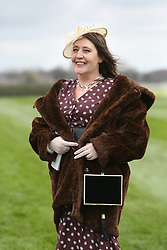 © Licensed to London News Pictures. 08/04/2016. Liverpool, UK. A women looks glamorous in a fur coat and hat on Ladies Day at the Grand National 2016 at Aintree Racecourse near Liverpool. The race, which was first run in 1839, is the most valuable jump race in Europe. Photo credit : Ian Hinchliffe/LNP