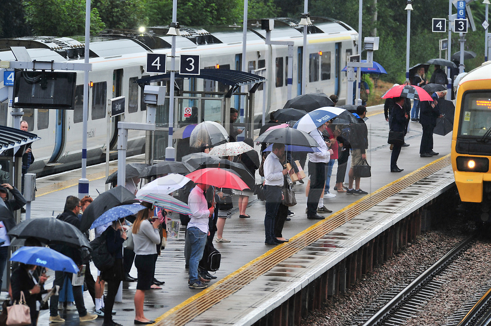 © Licensed to London News Pictures. 09/08/2018. Petts Wood, UK. Commuters shelter underneath umbrellas form the rain at Petts Wood train station, Petts Wood, south east London as the sunny weather is replaced with rain.<br /> Photo credit: Grant Falvey/LNP