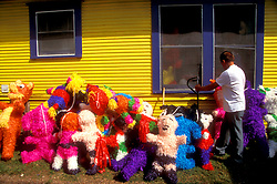 Stock photo of a man moving pinatas outside of the Farmer's Market in Houston Texas