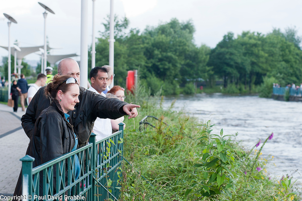 Torrential  rain causes the River Don to rise to within feet of overflowing its banks and attracts locals out to come and see the river at probably the highest level seen in the Meadowhall area of Sheffield since it burst it banks in 2007. ..6 July 2012.Image © Paul David Drabble