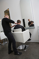 Unisex hairdresser  male client has his hair cut