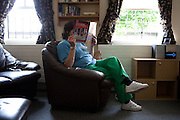 A prisoner reads a magazine in the lounge of one of the residential units. HMP Styal, Wilmslow, Cheshire