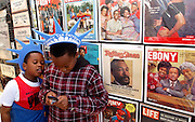 "1/14/06 -- TAMPA -- Quintin Williams, 6, watches his brother, Adrian, 9, play a cell phone game in front of a display of historic magazine covers featuring prominent black Americans at the Tampa Black Heritage Festival at Al Lopez Park on Jan. 14, 2006. Neither of the boys knew who any of the people on the cover were, but their mother bought one of the ""Separate But Equal"" signs for Quintin to use in show and tell. The display was owned by Blackmark, an Oklahoma City, Okla.,-based company that specializes in black history memorabilia. Photo by KELVIN MA/staff"
