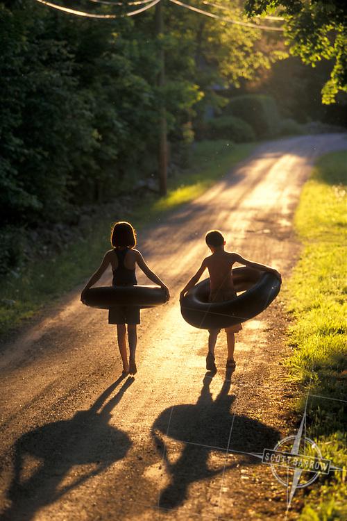 Siblings walking down path with innertubes