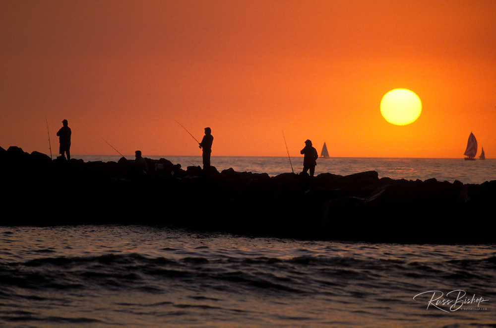 Silhouette of people fishing on jetty at sunset, Ventura, California USA