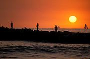 Silhouette of people fishing on jetty at sunset, Ventura, California USA