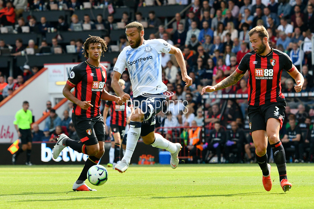Cenk Tosun (14) of Everton skips past Nathan Ake (5) of AFC Bournemouth and Steve Cook (3) of AFC Bournemouth during the Premier League match between Bournemouth and Everton at the Vitality Stadium, Bournemouth, England on 25 August 2018.