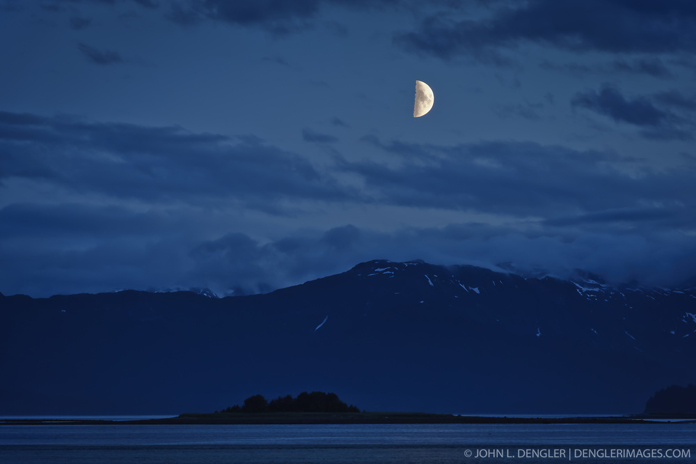 The moon sets over the Fairweather mountain range in Glacier Bay National Park and Preserve in this view seen from Kidney Island, located in the Beardslee Islands of the park in southeast Alaska.