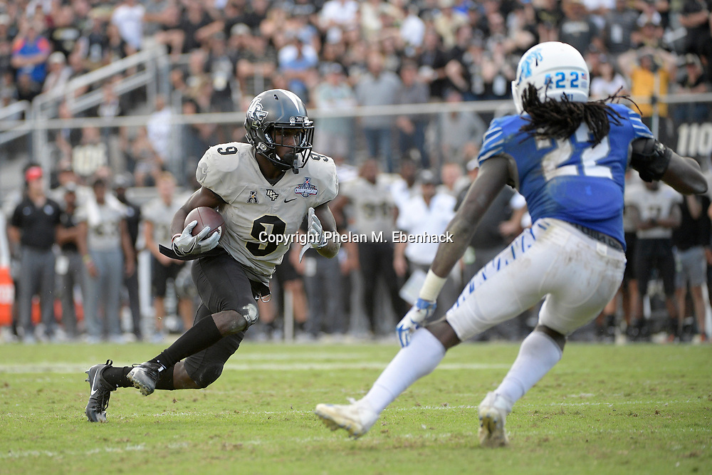 Central Florida running back Adrian Killins Jr. (9) rushes for yardage in front of Memphis defensive back Tyrez Lindsey (22) during the second half of the American Athletic Conference championship NCAA college football game Saturday, Dec. 2, 2017, in Orlando, Fla. Central Florida won 62-55. (Photo by Phelan M. Ebenhack)