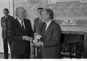 Charles Haughey Receives Seal Of Office.   (T3)..1989..12.07.1989..07.12.1989..12th July 1989..After winning the General Election and having been elected Taoiseach by a majority in Dail Eireann, Charles Haughey went to Aras an Uachtarain to accept the seal of office. The seal of office was granted by President Patrick Hillery...Image shows President Patrick Hillery and An Taoiseach, Charles Haughey,proudly displaying the seal of office to the waiting media.