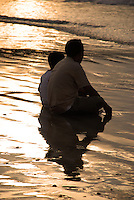 Peaceful scene of father and son at the beach at sunset in Bali, Indonesia.