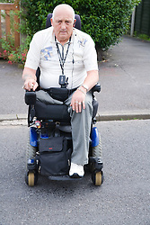 Male wheelchair user crossing the road,