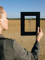 Businesswoman framing tree in desert back view