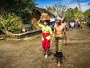 22 JULY 2016 - TENGANAN DUAH TUKAD, BALI, INDONESIA: A couple walks into pandanus fights in the Tenganan Duah Tukad village on Bali. The ritual Pandanus fights are dedicated to Hindu Lord Indra. Men engage in ritual combat with spiky pandanus leaves and rattan shields. They usually end up leaving bloody scratches on the combatants' backs. The young girls from the community wear their best outfits to watch the fights. The fights have been traced to traditional Balinese beliefs from the 14th century CE. The fights are annual events in the Balinese year, which is 210 days long, or about every seven months in the Gregorian calendar.    PHOTO BY JACK KURTZ