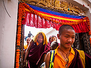 07 MARCH 2017 - KATHMANDU, NEPAL: Buddhist monks walk through a doorway in Boudhanath Stupa during a consecration ceremony. Boudhanath Stupa, the most important Buddhist site in Nepal and a popular tourist attraction, was consecrated Tuesday in a ceremony attended by thousands of Buddhist monks and Buddhist people from Nepal and Tibet. The stupa was badly damaged in the 2015 earthquake that devastated Nepal. The stupa, which reopened in November 2016, was repaired in about 18 months. The repair was financed by private donations raised by international Buddhist organizations.     PHOTO BY JACK KURTZ