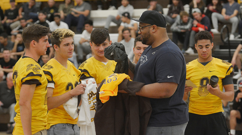 gbs050417e/SPORTS -- Cibola football players, from left, Steven Bitzer, Tyler Blanch, Jacob Padilla, Adan Baca  and Marcus Steel give Cibloa football clothing to current New England Patriots and Super Bowl Champion, Alan Branch, during a program honoring him at Cibola on Wednesday, May 3, 2017. (Greg Sorber/Albuquerque Journal)