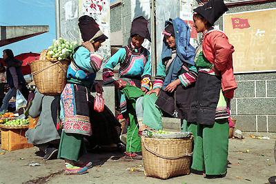 Chine, marche?.Dali, province du Yunnan, Chine. A? Dali, une des villes les plus visite?es du Yunnan, l'ethnie Bai est la plus nombreuse apre?s les Hans qui constituent 92% de la population chinoise. On voit ici un groupe de femmes Bai en grande discussion a? la sortie d'un marche?, portant leurs ve?tements traditionnels de tous les jours.