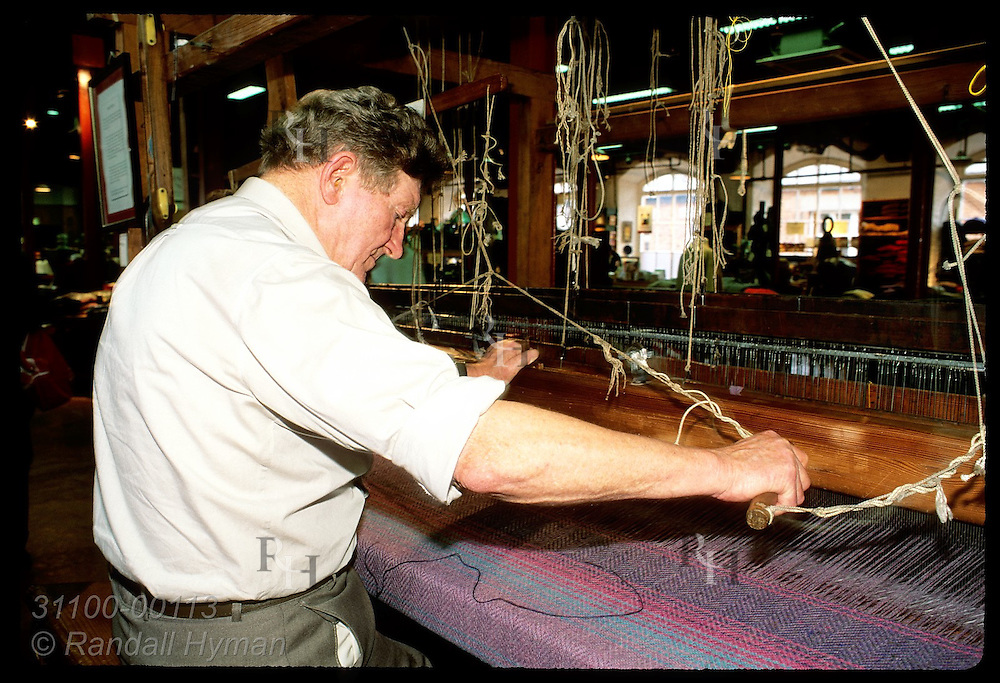 Man weaves textile on old loom for shoppers to watch at Blarney Woolen Mills store; Blarney. Ireland