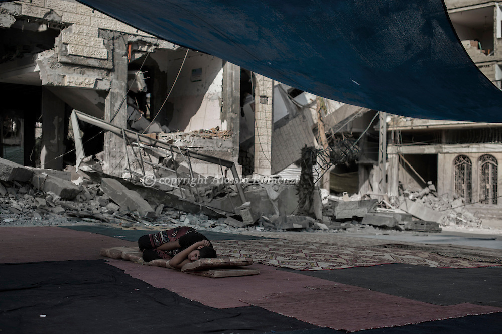 Gaza Strip, Gaza City: A Palestinian sleeps in front of the destroyed by Israeli airstrike Al-Shati Camp mosque in Gaza City on August 2, 2014. ALESSIO ROMENZI