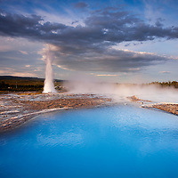 Iceland, Geysir, Rising sun lights deep blue thermal pool and steam venting from Strokkur Geyser on summer morning